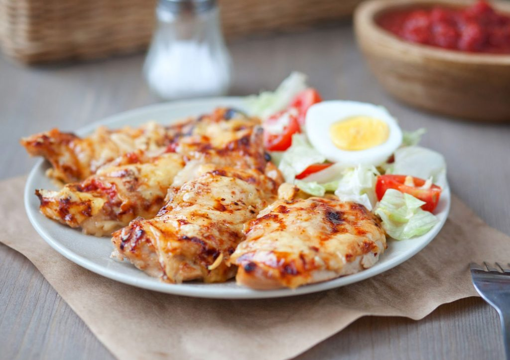 chicken breasts with melted cheese on top, salad, on white plate