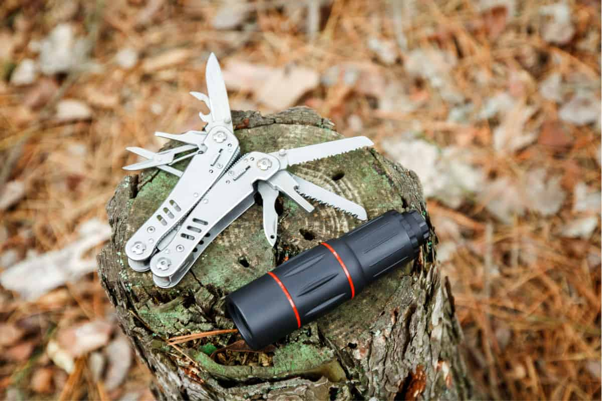 knife tool and monocular on tree stump