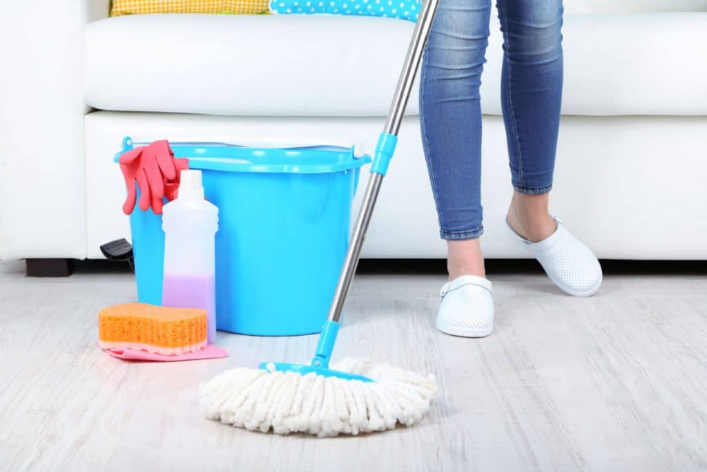 Cleaning floor in room close-up of womans feet and mop
