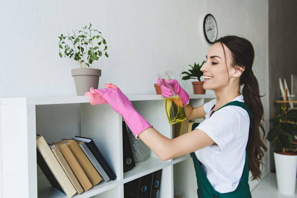 smiling woman wiping white bookshelves