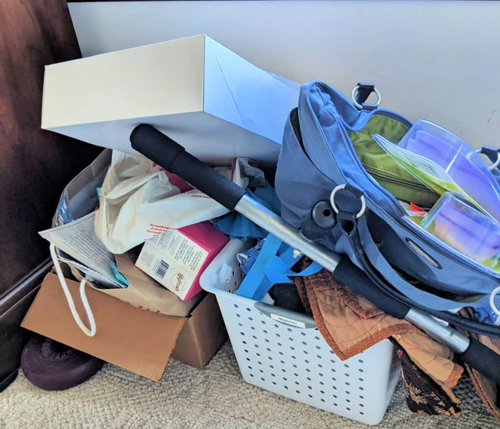 stack of clutter on white carpet, boxes, blue tote bag of stuff